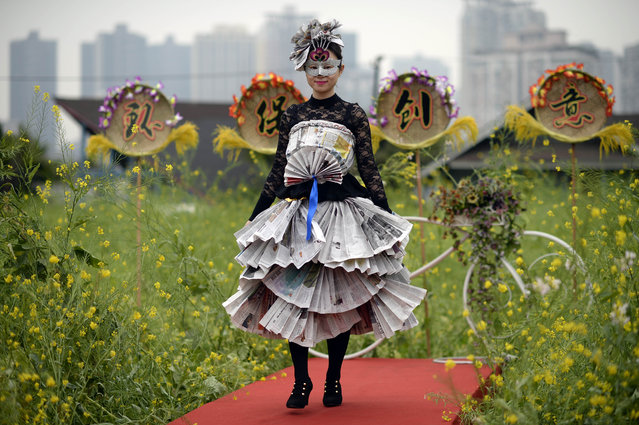 In this Thursday, March 19, 2015 photo, a worker in an outfit made from scrap material stands in a farm on the rooftop of a door manufacturer in Chongqing municipality in southwest China. (Photo by AP Photo)