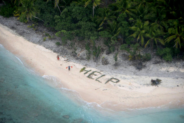 "MICRONESIA: Two of three men stranded on the uninhabited island of Fanadik in Micronesia wave life jackets next to palm fronds spelling the word ""HELP"" as a U.S. Navy P-8A Poseidon maritime patrol and reconnaissance aircraft discovers them, in this picture released by the U.S. Pacific Fleet taken April 7, 2016. Three days earlier, the the men's 19-foot skiff capsized after setting out to sea from Pulap. The men were later picked up by a local boat and returned to safety. (Photo by Reuters/US Pacific Fleet)"
