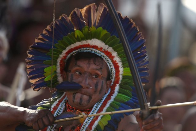 A Brazilian indigenous man participates in a bow and arch competition during the XII Brazilian Indigenous Games in Cuiaba, Brazil, 10 November 2013. 1,600 indigenous from 48 Brazilian ethnic groups will compete in ten traditional disciplines. (Photo by Fernando Bizerra Jr./EPA)