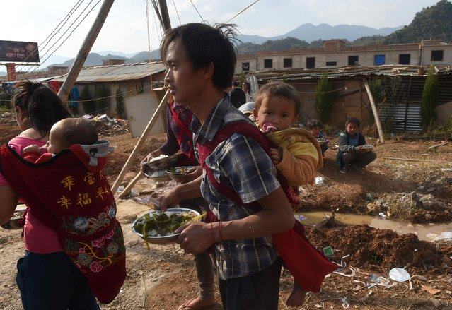 A man carries his child at a refugee camp at Myanmar's border town with China, in Kokang, February 16, 2015. (Photo by Reuters/Stringer)
