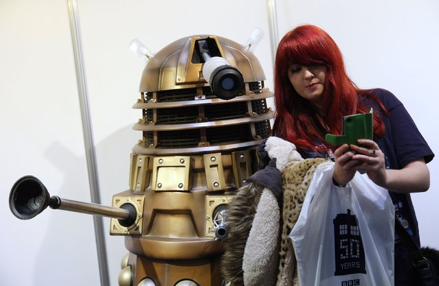 """A Doctor Who fan takes a """"selfie"""" photograph on her mobile phone with a Dalek at the 'Doctor Who 50th Celebration' event in the ExCeL centre on November 22, 2013 in London, England. The sold-out three day event in the ExCeL London convention centre celebrates 50 years of the show which has seen 11 actors play the role of Doctor Who and receives a worldwide cult following.  (Photo by Oli Scarff/Getty Images)"""