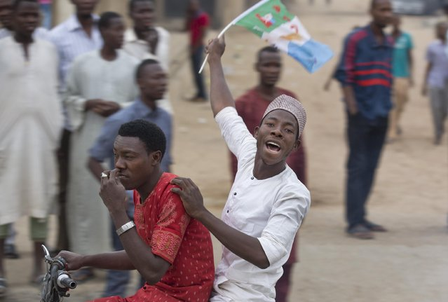 Supporters of opposition candidate Muhammadu Buhari riding on a motorcycle celebrate an anticipated win for their candidate, in Kano, Nigeria Tuesday, March 31, 2015. (Photo by Ben Curtis/AP Photo)