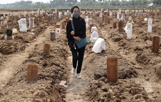 A woman walks among the graves of COVID-19 victims at the Rorotan Cemetery in Jakarta, Indonesia, Wednesday, July 7, 2021. Across the country, the coronavirus pandemic is again spreading rapidly with bursting beyond capacity and oxygen supplies are running out, leaving people do what they can to cope with caring for sick friends and relatives at home. (Photo by Tatan Syuflana/AP Photo)