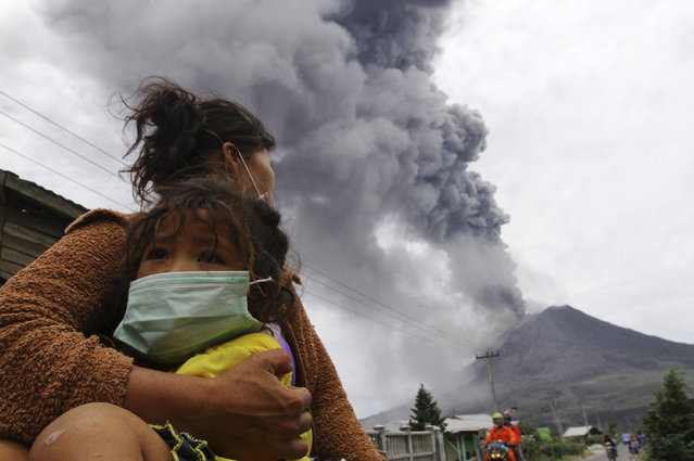 A mother holds her child as Mount Sinabung spews ash and hot lava during an eruption in Perteguhan village in Karo district, September 17, 2013. (Photo by Roni Bintang/Reuters)