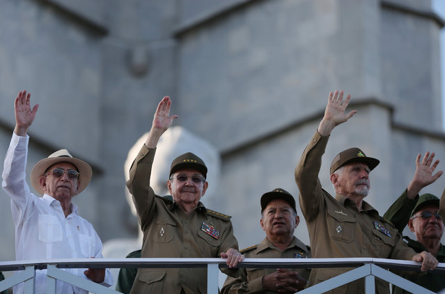 "Cuba's President Raul Castro waves together with Vice President Jose Ramon Machado Ventura (L), General Guillermo Garcia (3rdR) and Commander of the Revolution Ramiro Valdes (2ndR) as they watch a march to mark the Armed Forces Day and commemorate the landing of the yacht Granma, which brought the Castro brothers, Ernesto ""Che"" Guevara and others from Mexico to Cuba to start the revolution in 1959, in Havana, Cuba, January 2, 2017. (Photo by Alexandre Meneghini/Reuters)"