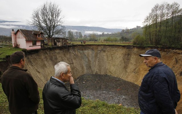 In this Thursday, November 21, 2013 photo, people gather around a huge sinkhole in the village of Sanica, Bosnia. Only weeks ago, the spot was a pond full of fish and floating green algae, lined with old willow and plum trees, and a grass field where cattle used to peacefully graze. (Photo by Amel Emric/AP Photo)