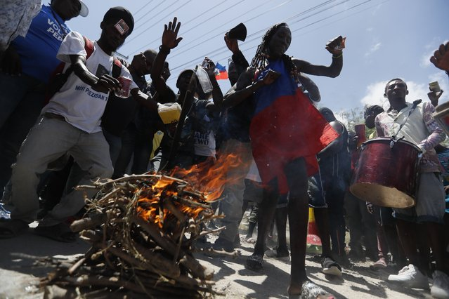 Supporters of former Haitian President Jean-Bertrand Aristide dance and drum as they wait near the airport for his expected arrival from Cuba, where he underwent medical treatment, in Port-au-Prince, Haiti, Friday, July 16, 2021. Aristide's return adds a potentially volatile element to an already tense situation in a country facing a power vacuum following the July 7 assassination of President Jovenel Moïse. (Photo by Fernando Llano/AP Photo)