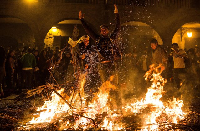 Parishioners jump over bonfires as they wait for the start of a procession during the Holy Week celebrations in Ayacucho, Peru, Sunday, April 5, 2015. Ayacucho has large religious celebrations during the Holy Week. These celebrations also include processions, fireworks, horse races and the a running of the bulls. (Photo by Sebastian Castañeda/AP Photo)