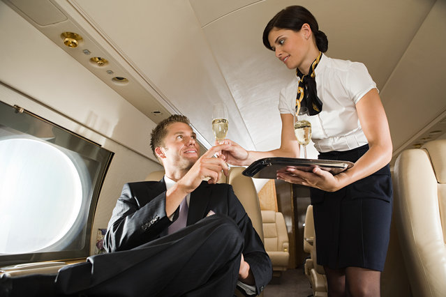 Stewardess handing champagne to man. (Photo by Image Source/Getty Images)