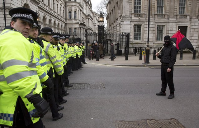 A protester walks along a police line as anti-fascist demonstrators stage a counter demonstration during a PEGIDA (Patriotic Europeans Against the Islamisation of the West) rally on Whitehall in central London April 4, 2015. (Photo by Neil Hall/Reuters)