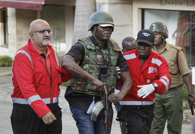 An injured member of the security forces is helped by paramedics at a hotel complex in Nairobi, Kenya Tuesday, January 15, 2019. Terrorists attacked an upscale hotel complex in Kenya's capital Tuesday, sending people fleeing in panic as explosions and heavy gunfire reverberated through the neighborhood. (Photo by Ben Curtis/AP Photo)