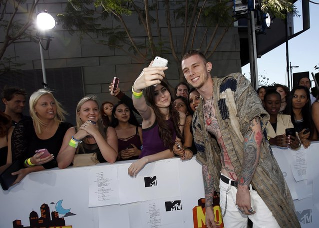 Rapper Machine Gun Kelly poses for fans as he arrives at the 2015 MTV Movie Awards in Los Angeles, California April 12, 2015. (Photo by Mario Anzuoni/Reuters)
