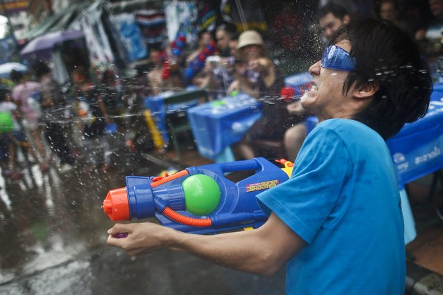 A man sprays water in the middle of a water fight as Thais and foreign tourists celebrate the water festival Songkran on the popular tourist strip of Khao San road on the first day of the water festival Songkran celebrations, the Thai traditional New Year, in Bangkok, Thailand, 12 April 2015. (Photo by Fazry Ismail/EPA)