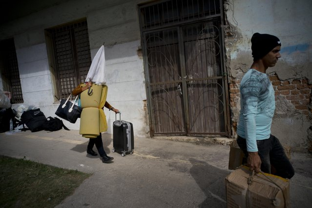 People affected by the destruction caused by the passing of a tornado, walk with their belongings to a bus to be taken to a shelter in Havana, Cuba, Monday, January 28, 2019. Neighborhood brigades and teams of government workers hacked at fallen trees and hauled chunks of concrete out of collapsed homes Monday as the Cuban capital attempted to recover from what officials called the strongest tornado to hit Cuba in nearly 80 years. (Photo by Ramon Espinosa/AP Photo)