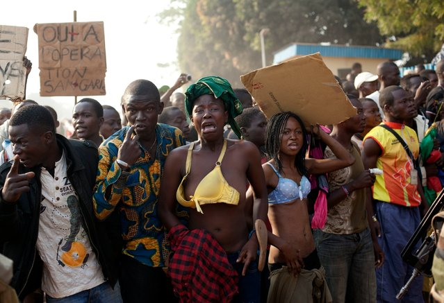 Women bare their chests in a traditional sign of placing a curse, after at least two people were injured by passing Chadian troops, during a protest outside Mpoko Airport in Bangui, Central African Republic, Monday, December 23, 2013. Hundreds of demonstrators gathered at the entrance to the airport Monday morning carrying signs protesting Chadian forces and expressing support for French troops and other regional African forces. At least two people were wounded as pickups of Chadian soldiers sped through the gathered crowd firing off several rounds. (Photo by Rebecca Blackwell/AP Photo)