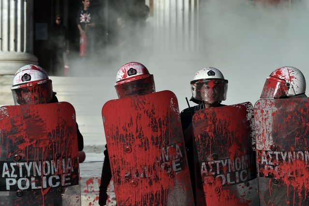 Riot policemen stand splattered with red paint thrown by protesters outside the Athens University on April 16, 2015. The protesters demended the release of families of political prisoners and changes to the anti-terrorist law. The tension arose at the end of the demonstration of opponents to a gold mine project in the Halkidiki peninsula, northern Greece, in Skouries. (Photo by Aris Messinis/AFP Photo)