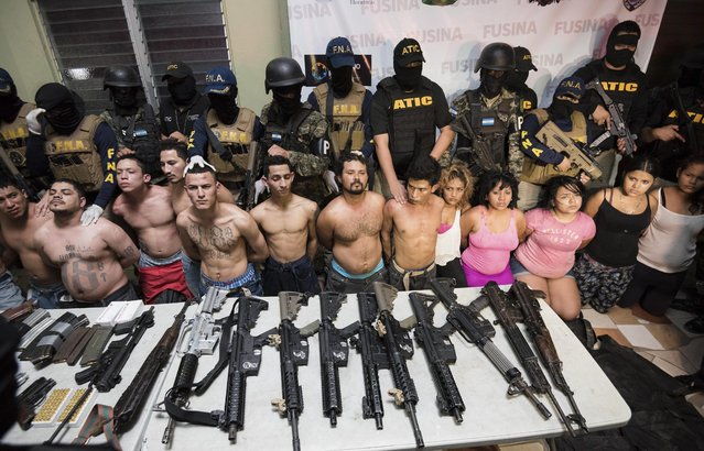 Members of the National Inter-Institutional Security Force (FUSINA) present alleged members of the gang Barrio 18, who were found to be in possession of illegal weapons in San Pedro Sula, Honduras, 18 January 2017. The alleged gang members were allegedly involved in the murder of Honduran journalist Igor Padilla, who, according to media reports, was shot dead 17 January by men wearing police uniforms. (Photo by Jordan Perdomo/EPA)
