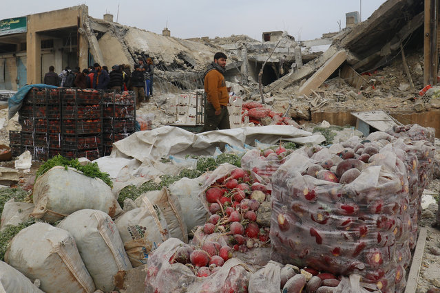 Men inspect damaged buildings near vegetables after an airstrike on a market in rebel held Maarrat Misrin city in Idlib province, Syria January 14, 2017. (Photo by Ammar Abdullah/Reuters)