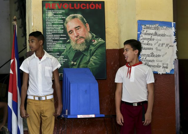 Schoolboys stand next to the ballot box at a polling station in Havana April 19, 2015. (Photo by Enrique de la Osa/Reuters)