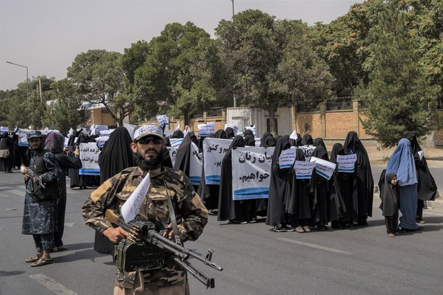 Armed Taliban fighters escort veiled women as they march during a pro-Taliban rally outside Shaheed Rabbani Education University in Kabul on September 11, 2021. (Photo by Bernat Armangue/AP Photo)