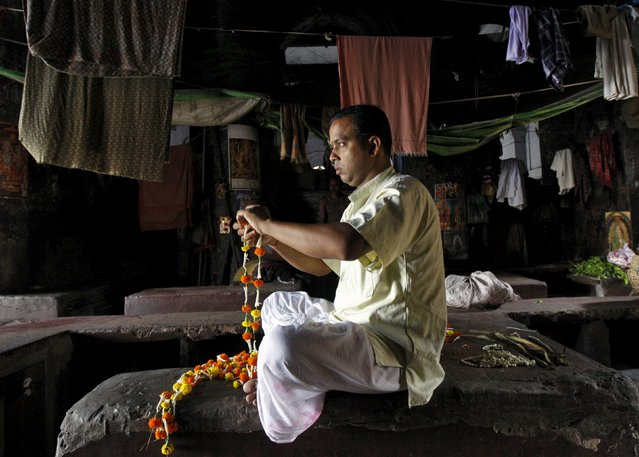 A Hindu priest makes garlands to use them in worshipping, near a flower market in Kolkata April 20, 2015. (Photo by Rupak De Chowdhuri/Reuters)