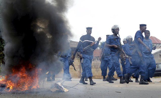 Riot policemen walk past a barricade during street protests against the decision made by Burundi's ruling National Council for the Defence of Democracy-Forces for the Defence of Democracy (CNDD-FDD) party to allow President Pierre Nkurunziza to run for a third five-year term in office, in the capital Bujumbura, April 26, 2015. (Photo by Thomas Mukoya/Reuters)