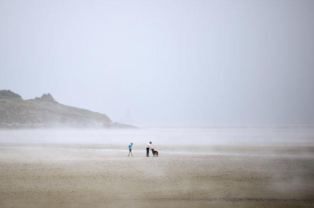 People walk through sea fog on Sandymount strand in Dublin, Ireland on July 1, 2021. (Photo by Clodagh Kilcoyne/Reuters)