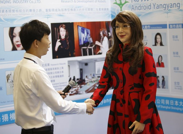 "A man shakes hands with a humanoid robot named ""Yangyang"" showing a facial expression, during its demonstration at the Global Mobile Internet Conference (GMIC) 2015 in Beijing, China,  April 29,  2015. (Photo by Kim Kyung-Hoon/Reuters)"