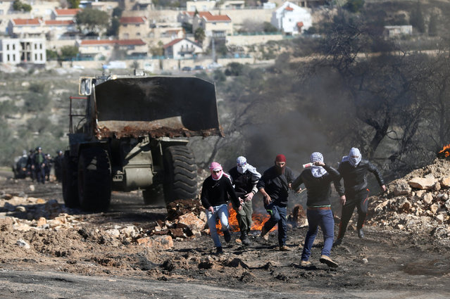 A Palestinian protester hurls a bottle containing liquid paint towards an Israeli vehicle as others run during clashes with Israeli troops following a protest against the near-by Jewish settlement of Qadomem, in the West Bank village of Kofr Qadom near Nablus February 3, 2017. (Photo by Mohamad Torokman/Reuters)
