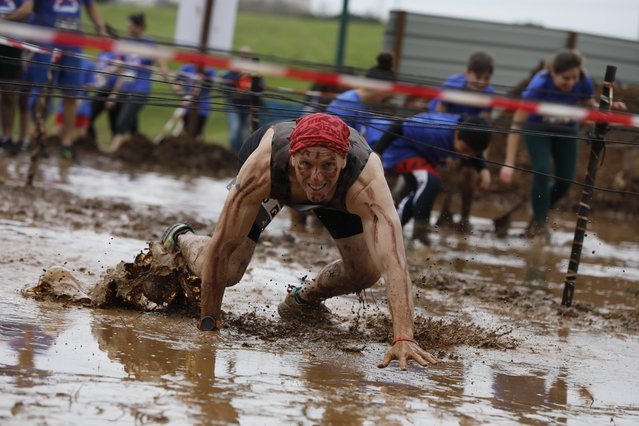 A participant makes his way through a muddy obstacle course during the Tel Aviv Mud Run race in the Yarkon Park, in Tel Aviv, Israel, 29 March 2019. (Photo by Abir Sultan/EPA/EFE)