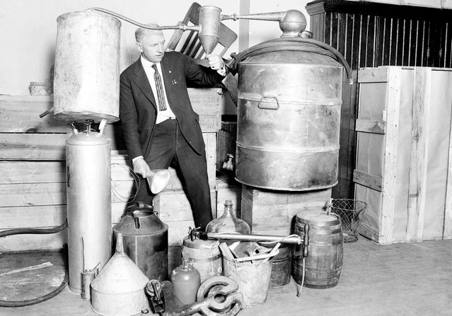 Edwin C. Arthur stands in the center of a collection of containers of moonshine taken during a South Side raid in Chicago, Illinois, 1922. From the Chicago Daily News collection. (Photo by Chicago History Museum/Getty Images)