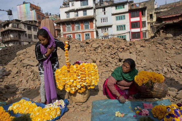 Nepalese flower vendors wait for customers at the Basantapur Durbar Square, damaged in the April 25 earthquake in Kathmandu, Nepal, Tuesday, May 5, 2015. (Photo by Bernat Amangue/AP Photo)