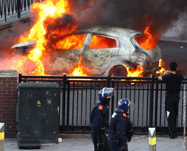 Police walk past a burning car during riots in Birmingham City Centre on August 8, 2011 in Birmingham, England