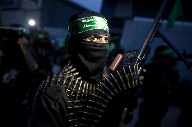 A member of the Ezzedine al-Qassam Brigades, the military wing of the Palestinian Islamist movement Hamas holds his weapon during a rally to mark the 12th anniversary of the death of assassinated Hamas spiritual leader Sheikh Ahmed Yassine on March 23, 2016 outside his home in Gaza city. (Photo by Mahmud Hams/AFP Photo)