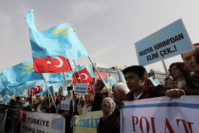 "Turks of Crimean Tatar origin waves Turkish and Crimean flags as they demonstrate to protest against Russia's military intervention in Crimea, Ukraine, in Ankara, Turkey, Sunday, March 2, 2014 The placard reads: ""Russia hand off Crimea!"" (Photo by Burhan Ozbilici/AP Photo)"