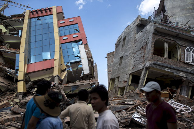 People walk past a collapsed building after a fresh 7.3 earthquake struck, in Kathmandu, Nepal, May 12, 2015. A 7.3 magnitude earthquake killed at least 37 people and spread panic in Nepal on Tuesday, bringing down buildings already weakened by a devastating tremor less than three weeks ago and unleashing landslides in Himalayan valleys near Mount Everest. (Photo by Athit Perawongmetha/Reuters)