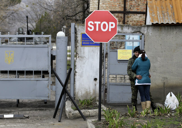 A Ukrainian soldier kisses a woman outside the infantry  base as Russian soldiers surround the a Ukrainian military infantry base in Perevalne, Ukraine, Tuesday, March 4, 2014. (Photo by Darko Vojinovic/AP Photo)