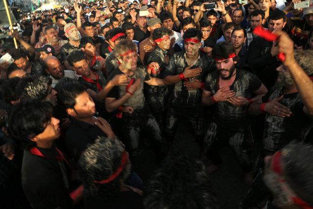 Shiite pilgrims beat their chests as they march towards the Imam Mousa al-Kazim shrine to commemorate his death, in the Shiite district of Kazimiyah, Baghdad, Iraq, Wednesday, May 13, 2015. (Photo by Karim Kadim/AP Photo)