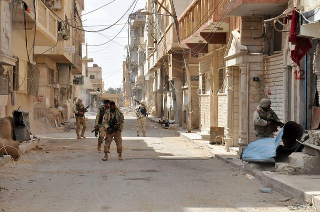 This photo released on Sunday March 27, 2016, by the Syrian official news agency SANA, Syrian government soldiers patrol a street in the ancient city of Palmyra, central Syria. The amount of destruction found inside the archaeological area in the historic town  was similar to what experts have expected but the shock came Monday from inside the local museum where the extremists have caused wide damage demolishing invaluable statues that were torn to pieces. (Photo by SANA via AP Photo)