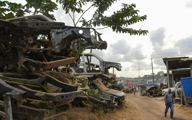 Residents walk past piles of destroyed vehicles in the Adjame neighborhood of Abidjan, on April 23, 2019. The Ivorian authorities plan to clear the city of Abidjan from wrecked cars to reduce pollution in the country. (Photo by Issouf Sanogo/AFP Photo)
