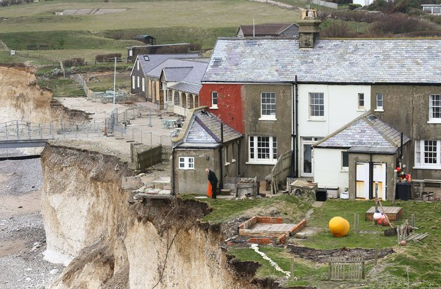 A resident of the cottage on the cliff edge at Birling Gap near Eastbourne, East Sussex, following more recent erosion in the area, on March 7, 2014. (Photo by Gareth Fuller/PA Wire)