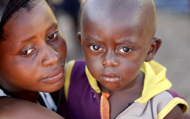 A Burundian refugee holds her son as they gather on the shores of Lake Tanganyika in Kagunga village in Kigoma region in western Tanzania with their belongings, as they wait for MV Liemba to transport them to Kigoma township, May 17, 2015. (Photo by Thomas Mukoya/Reuters)