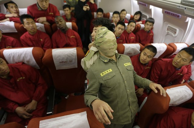 Trainees of the Tianjiao Special Guard/Security Consultant bodyguard training camp watch their instructor use a scarf to cover a student's head during a demonstration of close-quarter combat skills at a special course on flight safety inside a scale model of a passenger jet at a flight attendant training centre on the outskirts of Beijing, March 18, 2014. (Photo by Jason Lee/Reuters)