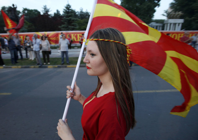 A woman with the national flag arrives at a rally in front of the Parliament building in Skopje, Macedonia, May 18, 2015. A massive pro-government rally was organized by Macedonia's rulling coalition led by conservative VMRO-DPMNE party, late Monday in Skopje. Macedonia faces one of its deepest political crises since gaining independence from Yugoslavia in 1991, stemming from opposition claims that the government illegally wire-tapped 20,000 people. (Photo by Boris Grdanoski/AP Photo)