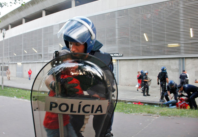 In this May 17 2015 photo, a riot policeman holds a crying boy as his father is attacked by other policemen with batons, right, outside of a stadium, in Guimaraes, Portugal. Portuguese prosecutors are investigating a policeman who beat a man in front of his young children and punched their grandfather outside a soccer stadium, sparking a national scandal. Police approached Jose Magalhaes. (Photo by Delfim Machado/AP Photo)