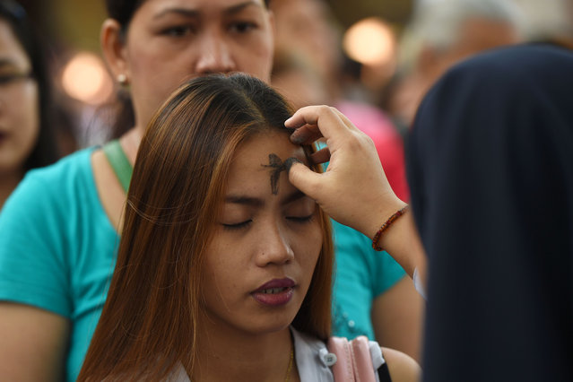 Catholic faithfuls queue to have their foreheads applied with ash by nuns on the observance of Ash Wednesday at a church ground in Manila on March 1, 2017. The 40- day period of Lent begins on Ash Wednesday, with Catholics around the world observing the season which culminates in Easter Sunday. (Photo by Ted Aljibe/AFP Photo)