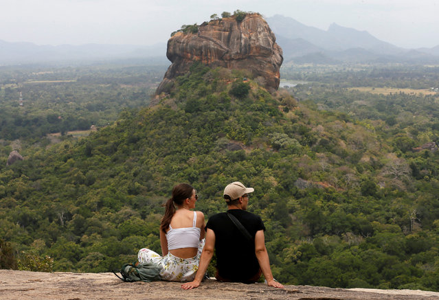 Two tourists rest on top of a rock as the Sigiriya Rock Fortress is seen in front of them, in Sigiriya, Sri Lanka July 30, 2018. (Photo by Dinuka Liyanawatte/Reuters)