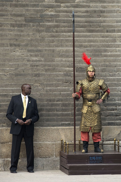 A U.S. secret service officer checks a Chinese performer dressed as an ancient warrior as U.S. first lady Michelle Obama visits a nearby city wall in Xi'an, in northwestern China's Shaanxi province, Monday, March 24, 2014. (Photo by Alexander F. Yuan/AP Photo)