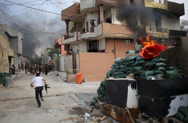 A Kurdish gunman runs across a street in Tuz Khurmato during clashes between Shi'ite militia and Kurdish gunmen, Iraq, April 24, 2016. (Photo by Goran Tomasevic/Reuters)