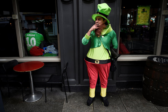 A man smokes a cigarette during the St. Patrick's day parade in Dublin, Ireland March 17, 2017. (Photo by Clodagh Kilcoyne/Reuters)